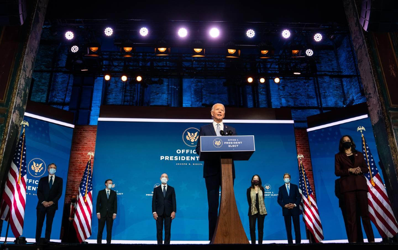 Joe Biden stands on stage with Kamala Harris, Anthony Blinken, Jake Sullivan, Alejandro Mayorkas, Avril Haines, John Kerry, and Linda Thomas-Greenfield