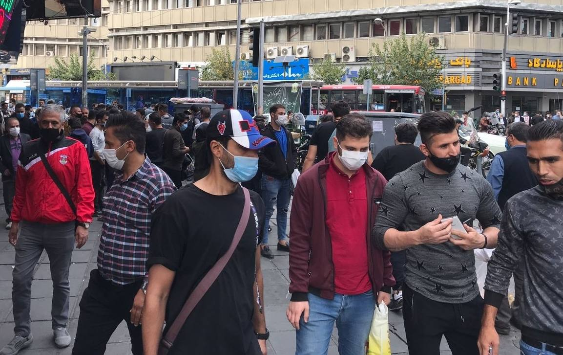 A group of people wearing face masks stand on a busy street.