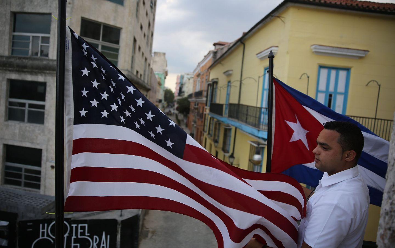 خوزه آلفردو بین پرچم آمریکا و پرچم کوبا ایستاده است