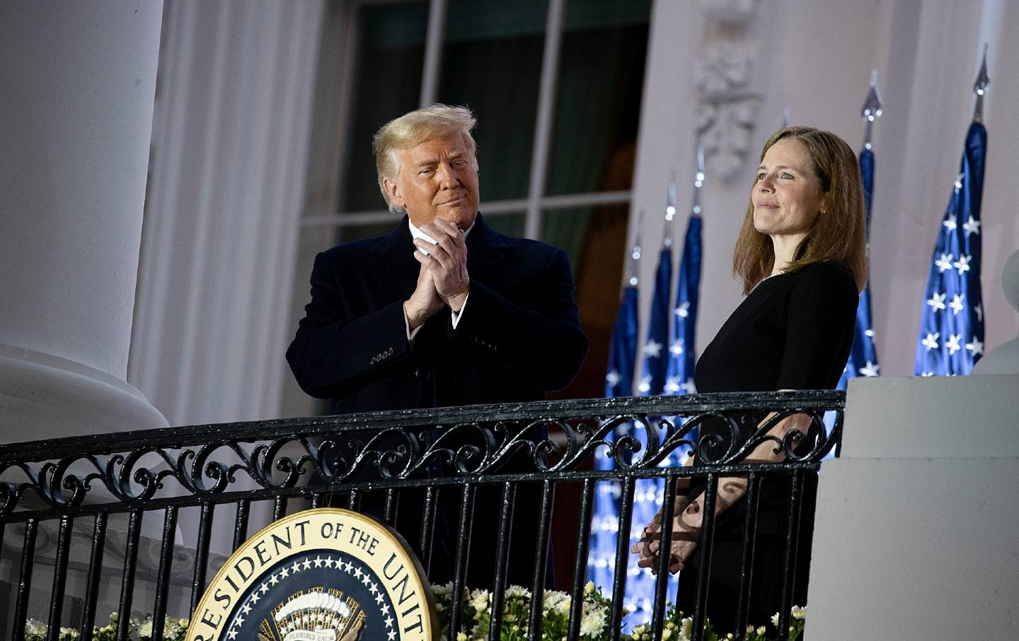 Trump and Amy Coney Barrett stand next to each other behind a gate.