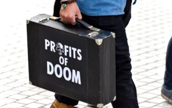 A man carries a briefcase with the words 'Profits of Doom'...